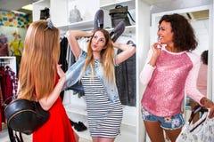 Groupe d'amies passant le temps ayant ensemble l'amusement faisant des achats Jolie fille montrant des oreilles avec des chaussur Photographie stock libre de droits
