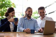Groupe d'amis à l'aide de l'ordinateur portable tout en ayant le café Photographie stock