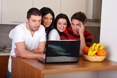 Groupe d'amis à l'aide de l'ordinateur portatif dans la cuisine Image stock