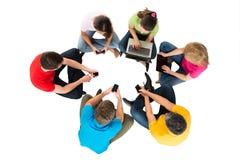 Groupe d'amis à l'aide des appareils électroniques Images stock
