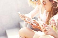 Groupe d'amis à l'aide des smartphones dans la ville Image stock
