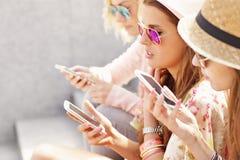 Groupe d'amis à l'aide des smartphones dans la ville Image libre de droits