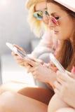 Groupe d'amis à l'aide des smartphones dans la ville Photographie stock libre de droits