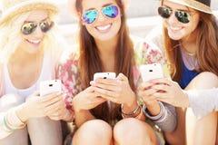 Groupe d'amis à l'aide des smartphones dans la ville Photos libres de droits