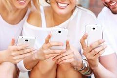 Groupe d'amis à l'aide des téléphones intelligents Photos libres de droits