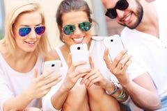 Groupe d'amis à l'aide des téléphones intelligents Photographie stock