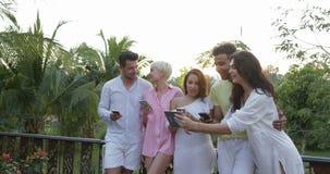 Groupe d'amis à l'aide des téléphones intelligents de cellules se tenant sur la terrasse au-dessus du paysage de coucher du solei banque de vidéos