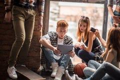 Groupe d'amis à l'aide des téléphones portables - étudiants s'asseyant dans une rangée et dactylographiant sur les smartphones Photographie stock