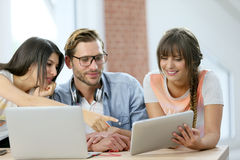 Groupe d'amis à l'aide du comprimé et de l'ordinateur portable Image libre de droits