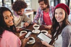 Groupe d'amis à l'aide du comprimé numérique et du téléphone portable Photo libre de droits