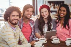 Groupe d'amis à l'aide du comprimé numérique tout en ayant la tasse de café Photographie stock
