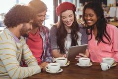 Groupe d'amis à l'aide du comprimé numérique tout en ayant la tasse de café Photo libre de droits