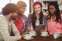Groupe d'amis à l'aide du comprimé numérique tout en ayant la tasse de café Photo stock