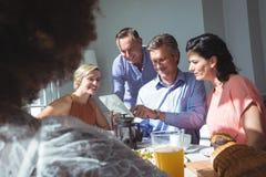 Groupe d'amis à l'aide du comprimé numérique tout en prenant le petit déjeuner Photographie stock libre de droits