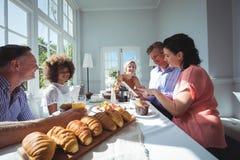 Groupe d'amis à l'aide du comprimé numérique tout en prenant le petit déjeuner Image stock