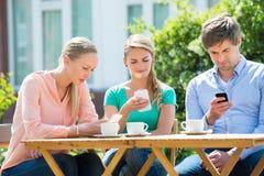 Groupe d'amis à l'aide du téléphone portable Images libres de droits
