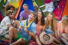 Groupe d'amis à l'aide du téléphone portable au terrain de camping Photos stock
