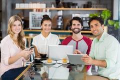Groupe d'amis à l'aide du téléphone portable, du comprimé numérique et de l'ordinateur portable Image stock