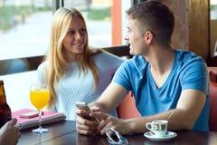 Groupe d'amis à l'aide du téléphone portable en café Photo stock