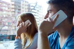 Groupe d'amis à l'aide du téléphone portable en café Image stock