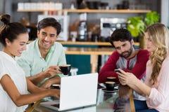 Groupe d'amis à l'aide du téléphone portable et de l'ordinateur portable Photos libres de droits