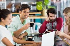 Groupe d'amis à l'aide du téléphone portable et de l'ordinateur portable Images stock