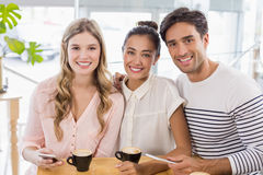 Groupe d'amis à l'aide du téléphone portable tout en ayant la tasse de café Photographie stock libre de droits