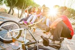 Groupe d'amis à la mode ayant l'amusement ensemble au parc de bmx de patin Images stock