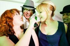 Groupe d'amis à la réception de karaoke Photo libre de droits
