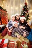 Groupe d'amis à Noël, nouvelle année se reposant sur l'esprit de plancher Photographie stock libre de droits