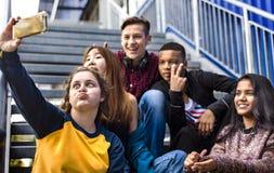 Groupe d'amis d'école ayant l'amusement et prenant un selfie Photo libre de droits