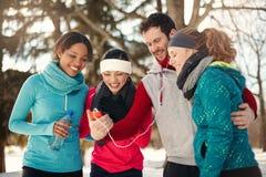 Groupe d'amis écoutant la musique dans la neige en hiver Photographie stock libre de droits