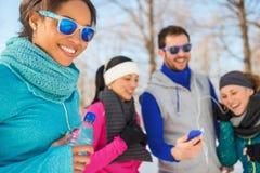 Groupe d'amis écoutant la musique dans la neige en hiver Photo libre de droits