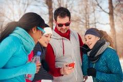 Groupe d'amis écoutant la musique dans la neige en hiver Photos stock