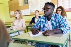 Groupe d'amis étudiant dans une salle de classe d'université Photographie stock libre de droits
