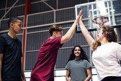 Groupe d'amis d'adolescent sur un terrain de basket se donnant de hauts cinq Photographie stock libre de droits