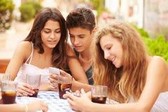 Groupe d'amis adolescents à l'aide du téléphone portable se reposant au ½ de ¿ de Cafï Photo stock