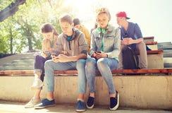 Groupe d'amis adolescents avec des smartphones dehors Image stock