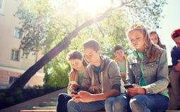 Groupe d'amis adolescents avec des smartphones dehors Images libres de droits