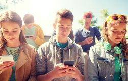 Groupe d'amis adolescents avec des smartphones dehors Photos libres de droits