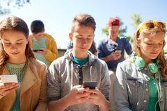 Groupe d'amis adolescents avec des smartphones dehors Photographie stock libre de droits