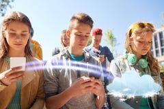 Groupe d'amis adolescents avec des smartphones dehors Photo stock