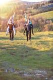 Groupe d'amis adolescents ayant des tours de ferroutage en Autumn Landscape Photographie stock libre de droits