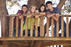 Groupe d'amis adolescents dans la cabane dans un arbre Photo stock