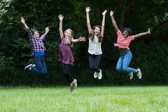Groupe d'amis adolescents féminins sautant dans le ciel Photo stock