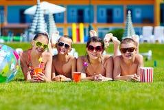 Groupe d'amis adolescents heureux se trouvant sur la pelouse d'été Image stock