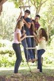 Groupe d'amis adolescents par la cabane dans un arbre Images libres de droits