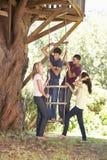 Groupe d'amis adolescents par la cabane dans un arbre Photos stock