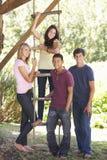 Groupe d'amis adolescents par la cabane dans un arbre Images stock