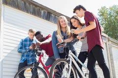 Groupe d'amis adolescents sur des vélos regardant des téléphones portables image stock